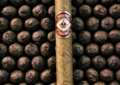Diamond Crown Cigar Standing in front of piles of rolled cigars