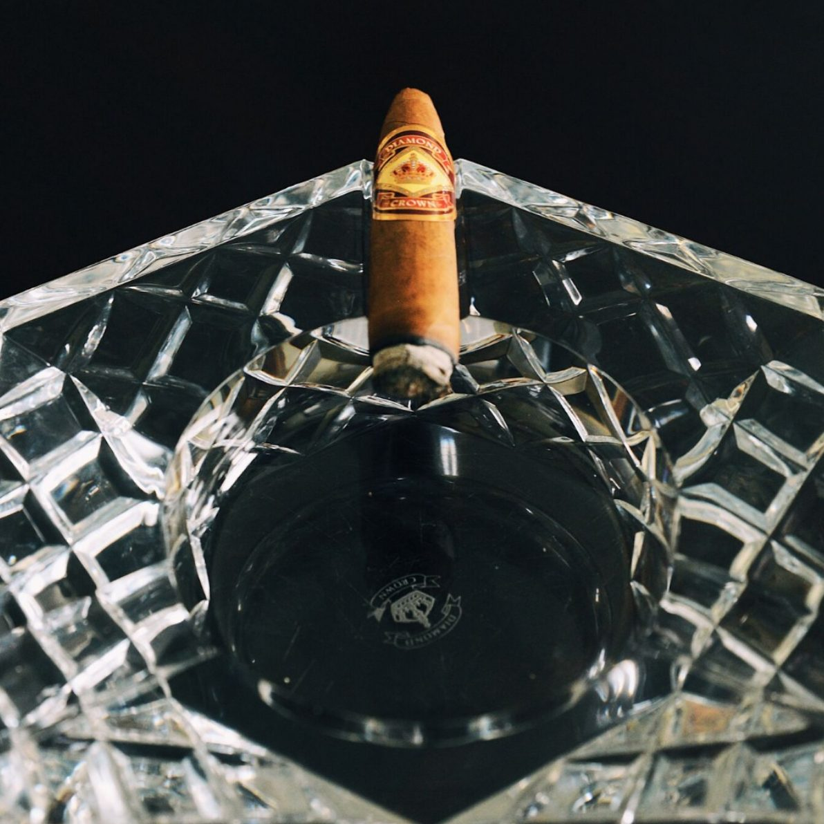 Diamond Crown Torpedo Cigar Resting on Crystal Ashtray.