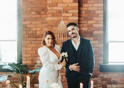 bride and groom standing behind wedding set up