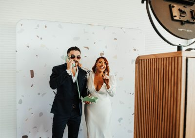 bride and groom with cigar and phone at photobooth